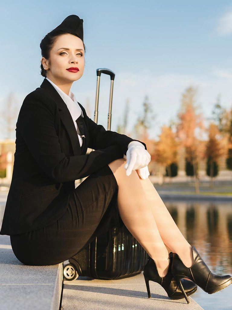 Attractive confident stewardess in uniform
