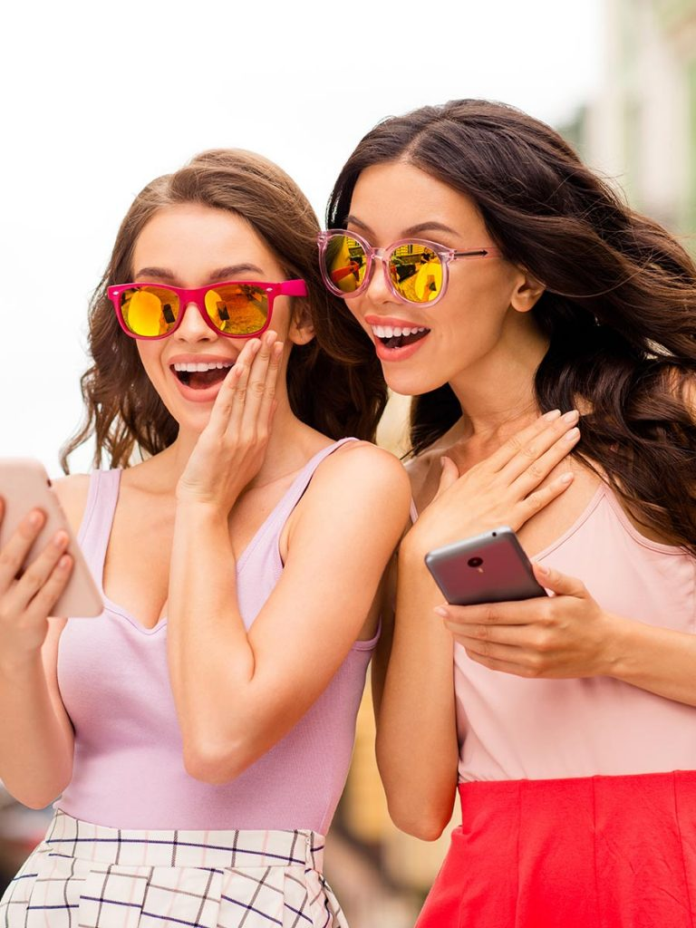 Zwei hübsche Frauen chaten auf ihrem Smartphone