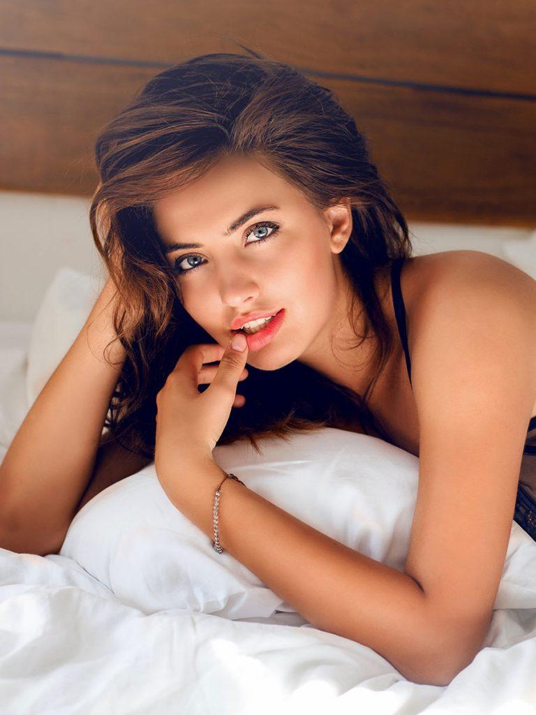 Attraktive junge Frau liegt im Bett